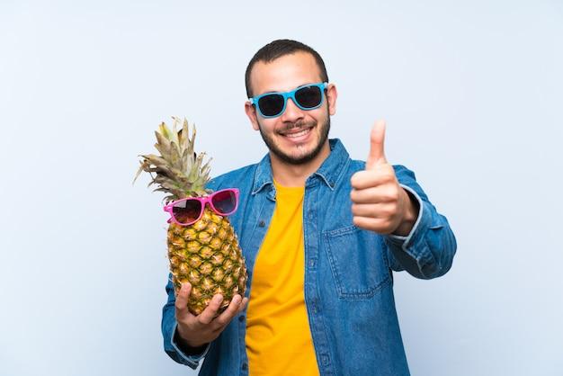 Der kolumbianische mann, der eine ananas mit der sonnenbrille gibt daumen hält, up geste und das lächeln