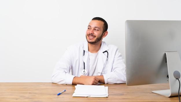 Der kolumbianische mann doktors, der zweifel macht, gestikulieren das schauen der seite