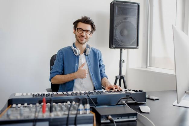 Der komponist gibt den daumen auf das studio