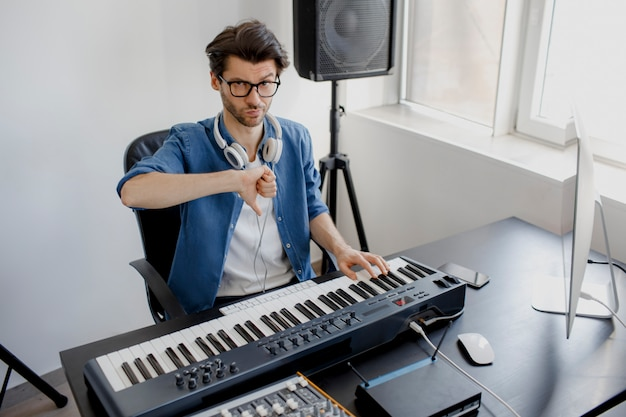 Der komponist zeigt mit dem daumen nach unten auf das studio
