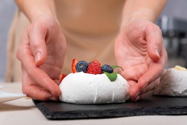 Der konditor bereitet einen delikaten kuchen mit frischen beeren zu. kuchen anna pavlova. nahaufnahme.