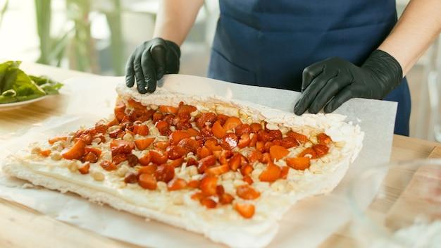 Der konditor bereitet einen kuchen mit buttercreme-nüssen und erdbeeren zu