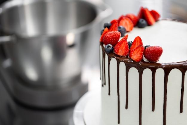 Der konditor dekoriert den kuchen mit schokoladenstreifen von erdbeeren und blaubeeren.