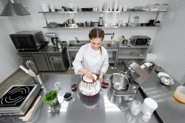 Der konditor dekoriert den kuchen mit schokoladenstreifen von erdbeeren.