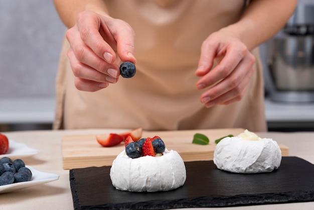 Der konditor dekoriert kuchen mit frischen beeren. prozess der herstellung von kuchen.