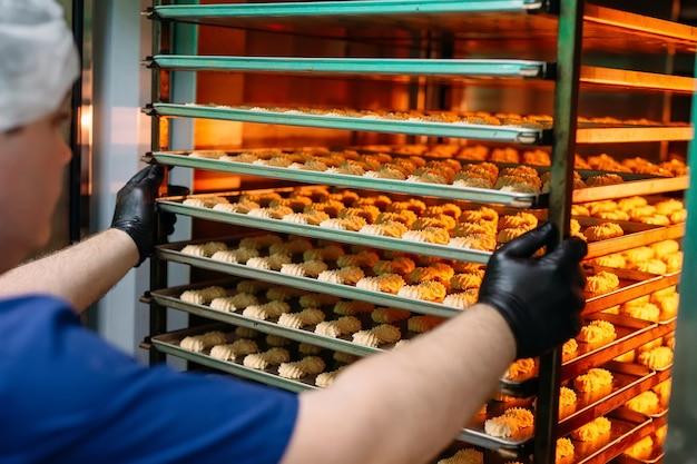 Der konditor holt fertige shortbread-kekse aus dem ofen.