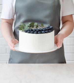 Der konditor in einer schürze und einem weißen t-shirt hält einen weißen kuchen in der hand auf einem ständer.