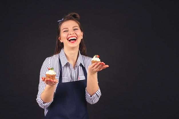 Der konditor lächelt in die kamera im studio auf einem schwarzen hintergrund und hält cupcakes in trauben