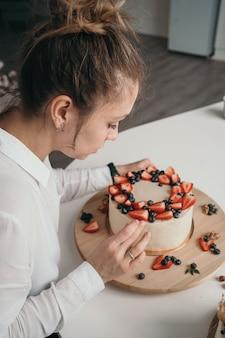 Der konditor macht einen kuchen zu hause leckeren frischkäsekuchen mit handgemachten beeren mädchen lernt kuchen backen