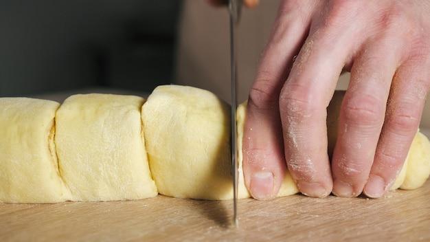 Der konditor schneidet brötchen mit zimt, zucker und butter auf portionen, um zimtschnecken zu backen. hände nahaufnahme.
