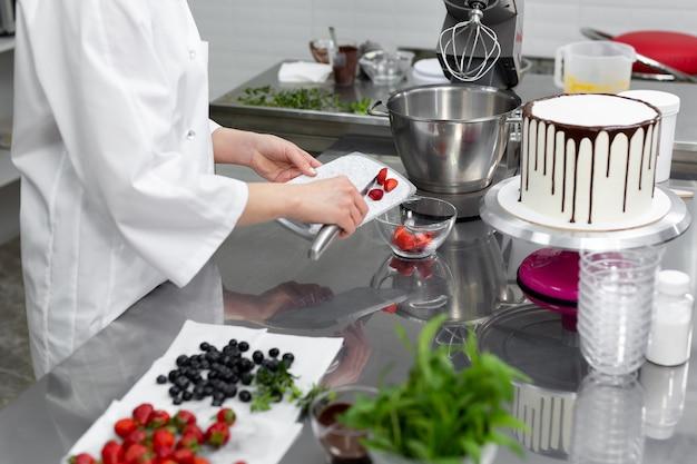 Der konditor schneidet erdbeeren, um den kuchen zu dekorieren