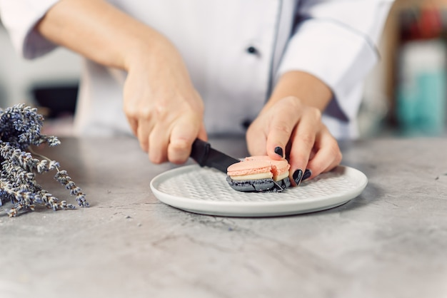 Der konditor schneidet macaron mit einem messer. schließen sie die hände der köchin. zubereitung eines leckeren desserts.