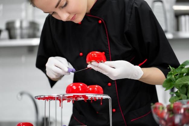 Der konditor überzieht den mousse-kuchen mit einer spiegelglasur.