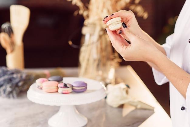 Der konditor verbindet die teile der macarons mit einer creme miteinander. schließen sie herauf bäckerhände, die macarons machen.