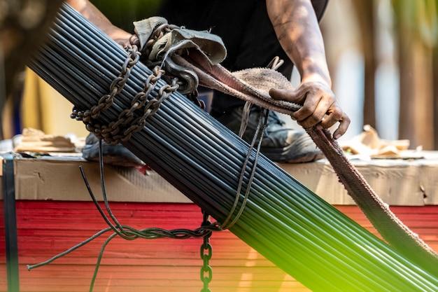 Der konstrukteur verriegelt die stahlstange mit der kette, bevor er mit dem kran angehoben wird