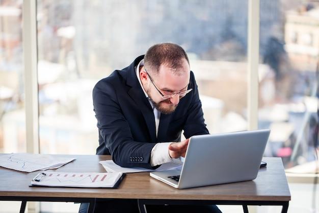 Der konzernverrückte sitzt im büro am computer und dreht durch, das emotionale portrait des mannes am tisch. verrückter arbeiter an seinem arbeitsplatz