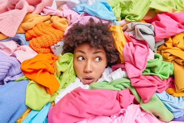 Der kopf der frau, der durch verschiedene mehrfarbige kleidung herausragt, sieht mit fassungslosem ausdruck weg weibliche shopaholic posiert um kleidung