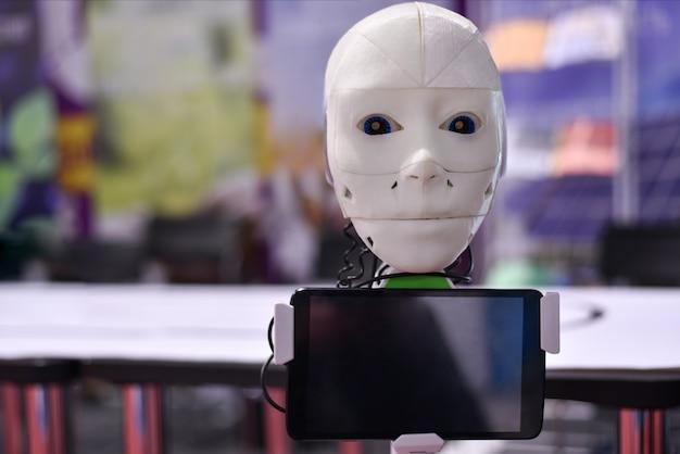 Der kopf des android-roboters kommuniziert mit der person über das tablet