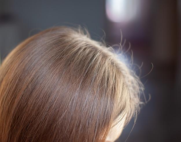 Der kopf einer frau mit einem scheitel grauen haares, dessen wurzeln aufgrund der quarantäne gewachsen sind.