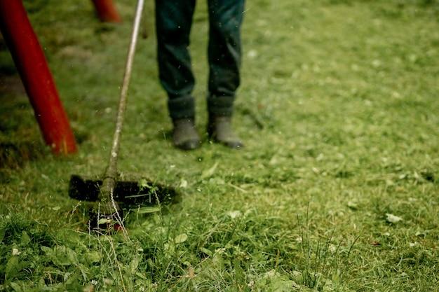 Der kopf eines benzin-manuellen rasenmähers beim arbeiten vor dem hintergrund von frisch gemähtem gras.