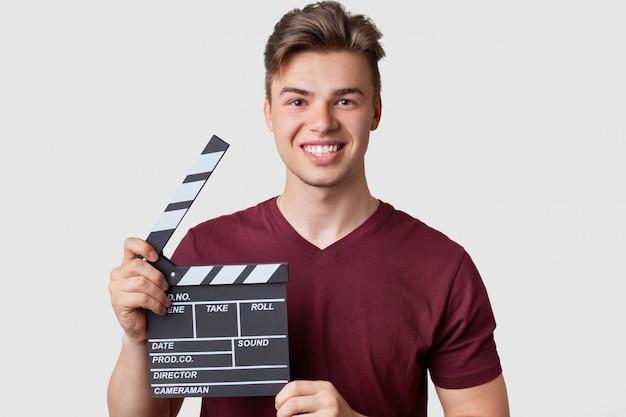 Der kopfschuss des gutaussehenden kameramanns hat einen trendigen haarschnitt, ist in ein lässiges outfit gekleidet, hält eine klappe für filmaufnahmen, models und hat ein zahniges lächeln. junger männlicher regisseur innen