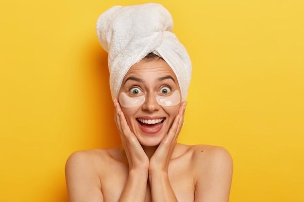 Der kopfschuss einer attraktiven jungen frau verbessert die hautqualität, berührt die wangen, schaut glücklich, trägt kosmetische schwämme unter den augen auf, hat hautpflege-routine, verwöhnt sich gerne