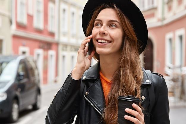 Der kopfschuss einer passagierin führt ein telefongespräch, sieht irgendwo glücklich aus und steht vor dem verschwommenen stadtraum