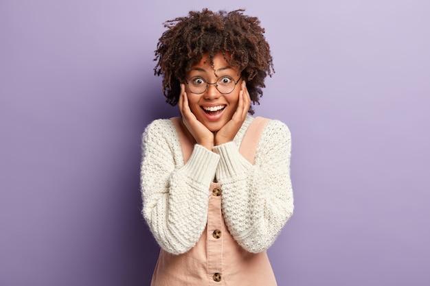Der kopfschuss einer überglücklichen, fröhlichen, afroamerikanischen, dunkelhäutigen frau berührt die wangen mit beiden händen, sieht glücklich aus, überrascht und glücklich, ein wunderbares geschenk zu erhalten, isoliert über der lila wand
