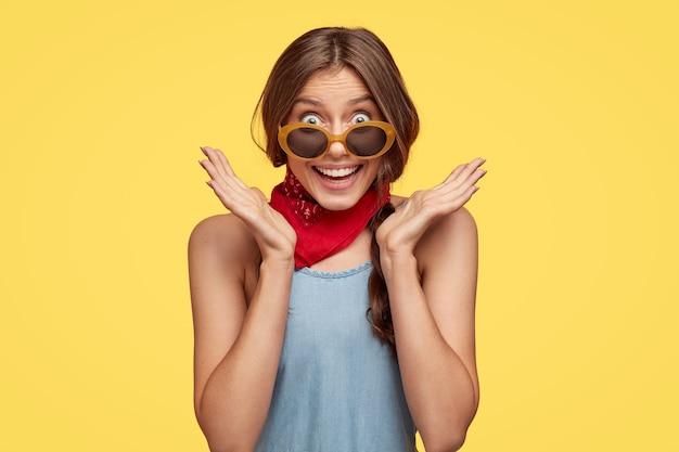 Der kopfschuss einer verblüfften fröhlichen europäischen frau breitet die hände in der nähe des gesichts aus, lächelt breit, bemerkt etwas angenehmes, trägt eine trendige sonnenbrille, isoliert über der gelben wand, drückt positivität aus