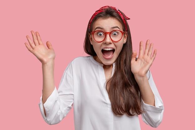 Der kopfschuss einer verblüfften schönen frau ruft vor glück aus, hebt die hände, fühlt sich verrückt und überglücklich, trägt eine brille, ein weißes hemd und hat einen fröhlichen gesichtsausdruck. menschen