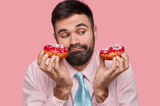 Der kopfschuss eines attraktiven jungen mannes hat einen verwirrten gesichtsausdruck, hält leckere donuts, sieht verwirrend aus und hat versuchungen