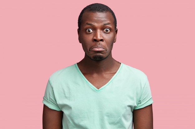 Der kopfschuss eines fassungslosen, missfallenen afroamerikaners krümmt die lippen, hört etwas unerwartetes, drückt überraschung aus, ist lässig gekleidet und sieht finster aus.