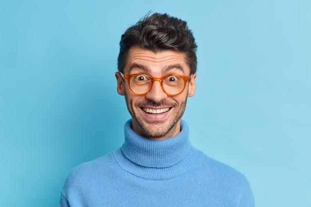 Der kopfschuss eines fröhlichen hipster-typen mit borstenlächeln reagiert im großen und ganzen positiv