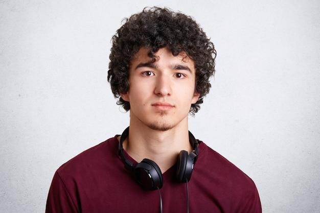 Der kopfschuss eines lockigen männlichen teenagers hat kopfhörer am hals, hört gerne musik in der freizeit und trägt freizeitkleidung