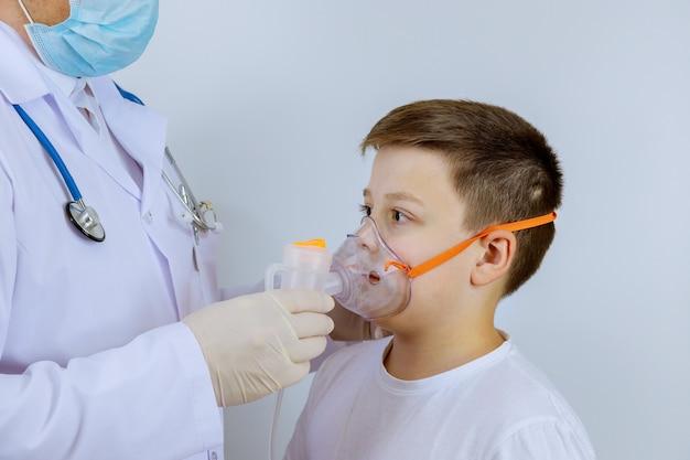 Der krankenhausarzt hilft einem kinderpatienten, auf einer sauerstoffmaske durchzuatmen.