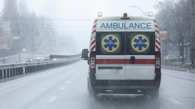 Der krankenwagen fährt mit hoher geschwindigkeit die straße entlang.