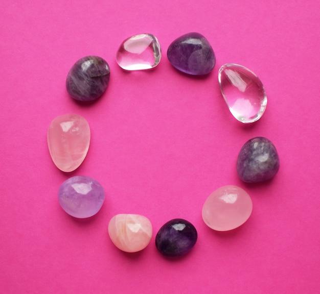 Der kreis ist mit natürlichen mineralien ausgekleidet. halbedelsteine in verschiedenen farben verarbeitet. amethyst und rosenquarz. rahmen aus edelsteinen auf leuchtend rosa hintergrund.