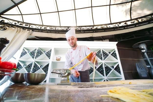 Der küchenchef bereitet die paste für die besucher vor.