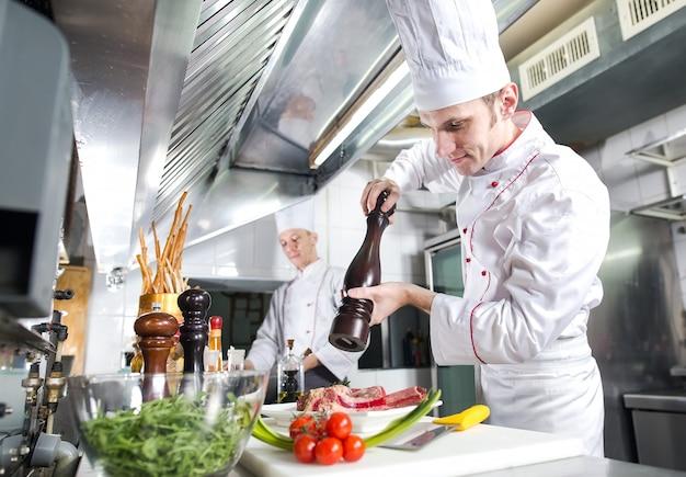 Der küchenchef bereitet ein gericht in der küche des restaurants zu.