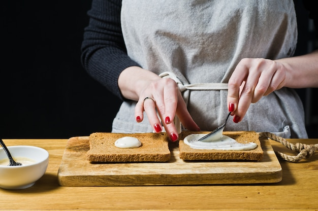 Der küchenchef bereitet ein sandwich mit schwarzbrot zu und schmiert die sauce auf toast.