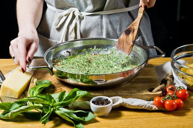 Der küchenchef bereitet eine sauce aus spinat und sahne, penne pasta.