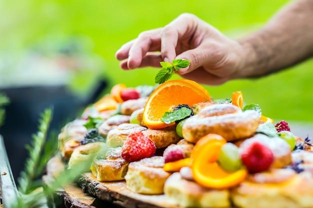 Der küchenchef bereitet einen teller kuchen mit frischen früchten zu. er arbeitet an der kräuterdekoration. gartenparty im freien.