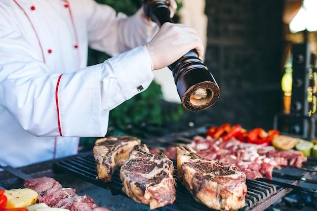 Der küchenchef bereitet fleisch auf dem grill zu.