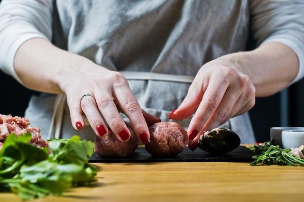 Der küchenchef bereitet fleischbällchen aus rohem hackfleisch zu.