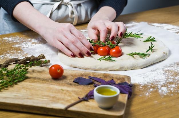 Der küchenchef bereitet focaccia zu und legt tomaten auf den teig.