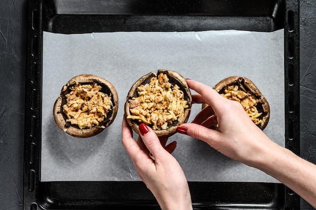 Der küchenchef bereitet gefüllte portobello-pilze zu. grauer hintergrund. ansicht von oben