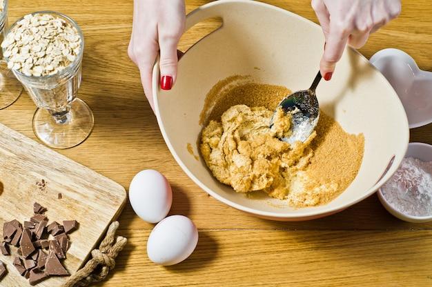 Der küchenchef bereitet haferkekse zu, mischt rohrzucker und butter.