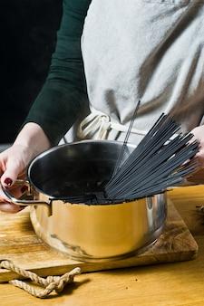 Der küchenchef bereitet schwarze nudelspaghetti zu