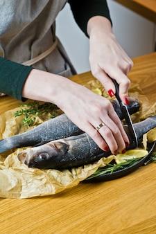 Der küchenchef bereitet wolfsbarsch auf einem holztisch zu.