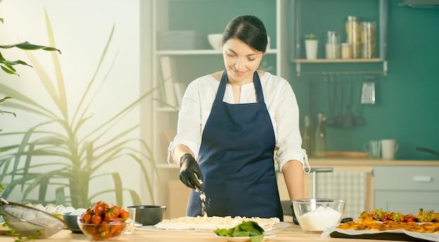 Der küchenchef bestreut den kuchen mit nüssen gemütliches modernes kücheninterieur